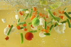 Vegetables splash in water soup cooking concept Stock Photography