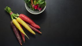Vegetables on table. Colorful carrots and radishes bunched together on table alongside a bowl dill leaves, spinach and radishes Stock Images