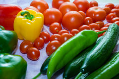 Vegetables on a table. Red tomatoes, yellow and green paprika, cucumbers on a table with drops of water Royalty Free Stock Photography