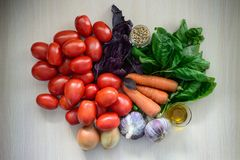 Vegetables on a table. Tomatoes carrots oil onion garlic grain salad Royalty Free Stock Images