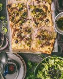 Vegetables tart with leek, served with green salad and dressing on rustic kitchen table background, top view. Tarte flambee - rustic french pie. Vegetarian royalty free stock image