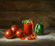 Vegetables and tomato juice. Still life with tomatoes, bell peppers and a glass of tomato juice Royalty Free Stock Image