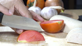 Vegetables tomatoes being cut into pieces stock video