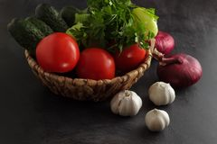 Vegetables tomatoes, cucumbers, onions and garlic with parsley in a basket Royalty Free Stock Photo