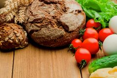 Mixed vegetables and two breads on kitchen table royalty free stock photo