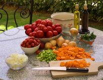 Vegetables, tomatoes, onions, chopped celery, carrot and basil leaves on the table with bottles of olive oil and balsamico vinegar. Preserving jars, cooking stock images