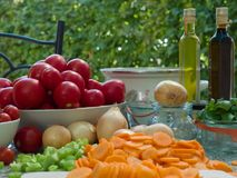 Vegetables, tomatoes, onions, chopped celery, carrot and basil leaves on the table with bottles of olive oil and balsamico vinegar. Preserving jars, cooking stock photography
