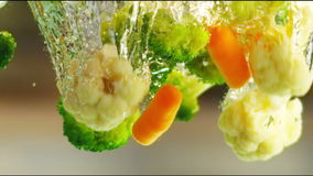 Vegetables in water. Slow motion close up shot of vegetables falling into the water