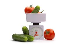 Vegetables on weights. Vegetables on the scales on a white background Stock Photos