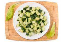 Vegetables on white background. Cucumbers, greens, cutting board, plate on a white background Royalty Free Stock Photo