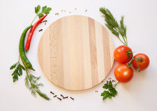 Vegetables on a white background. Cutting board, tomato and chili, dill and parsley, spice on the white background Stock Image