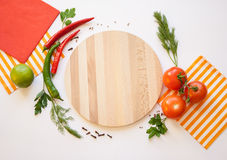 Vegetables on a white background and Cutting board. Cutting board, tomato and chili, dill and parsley, spice and striped and red napkins on the white background Royalty Free Stock Photography