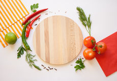 Vegetables on a white background and Cutting board. Cutting board, tomato and chili, dill and parsley, spice and striped and red napkins on the white background Stock Photography
