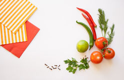 Vegetables on a white background. Tomato and chili, dill and parsley, spice, striped and red napkins on the white background Stock Image