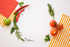 Vegetables on a white background. Tomato and chili, dill and parsley, spice, striped and red napkins on the white background Royalty Free Stock Photography