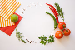 Vegetables on a white background. Tomato and chili, dill and parsley, spice, striped and red napkins on the white background Royalty Free Stock Images