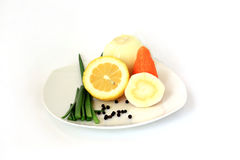 Vegetables on a white plate. The cleared onions, green onions, carrots, root of parsley and half lemon on a white plate. Horizontally Stock Photos