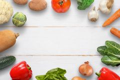 Vegetables on white wooden desk. Space for text in the middle.  Royalty Free Stock Photography