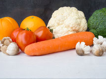 Vegetables on white wooden table. Tomato,carrot,mushroom,broccoli and cauliflower vegetables on white wooden table for healthy food concept with copy space Stock Photo