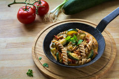 Vegetables with whole grain pasta in a rustic pan on a wooden  Royalty Free Stock Photo