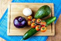 Vegetables on wooden background from above. Onion, cucumber, avocado, garlic and cherry tomatoes on wooden background from above Stock Photo