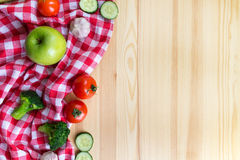 Vegetables on the wooden background. And red tartan tablecloth Stock Images