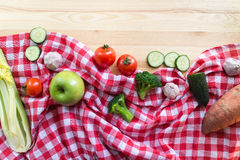 Vegetables on the wooden background. And red tartan tablecloth Royalty Free Stock Photos