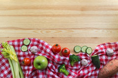 Vegetables on the wooden background. And red tartan tablecloth Stock Photos