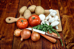 Vegetables on the wooden board. Tomato mushroom onion parsley potatoes on the board Stock Images