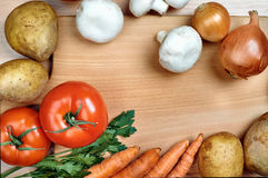 Vegetables on the wooden board. Tomato mushroom onion parsley potatoes on the board Stock Photography