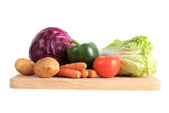 Vegetables on wooden chopping board Stock Images
