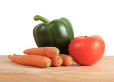 Vegetables on wooden chopping board Stock Photos