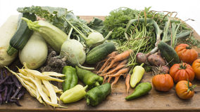 Vegetables on wooden chopping board. Several vegetables on display on wooden chopping board and table Royalty Free Stock Image