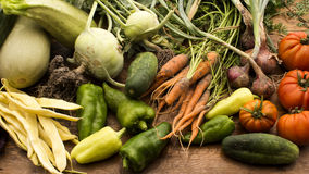 Vegetables on wooden chopping board. Several vegetables on display on wooden chopping board and table Stock Image