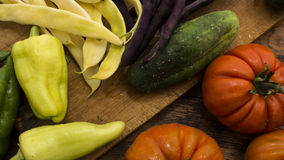 Vegetables on wooden chopping board. Several vegetables on display on wooden chopping board and table Stock Photography