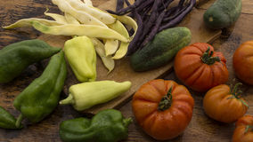 Vegetables on wooden chopping board. Several vegetables on display on wooden chopping board and table Stock Photos