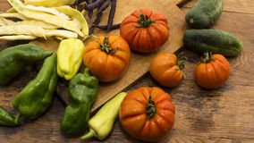 Vegetables on wooden chopping board. Several vegetables on display on wooden chopping board and table Stock Photo