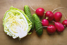 Vegetables on wooden cutboard, cucumbers, radishes, cabbage Royalty Free Stock Image