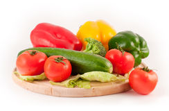 Vegetables on a wooden cutting plate. Different vegetables on a plate Stock Photo