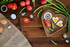 Vegetables and wooden plate with fried eggs on wooden background overhead close up shoot Royalty Free Stock Image