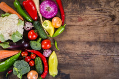 Vegetables on wooden table. Plenty of colorful vegetables on wooden background Stock Image