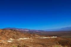Vegetación escasa y una bobina del camino de tierra hacia el horizonte en el altiplano boliviano contra la perspectiva de las mon imágenes de archivo libres de regalías