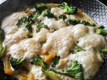 Vegetais com creme em uma bandeja quente, em uns brócolis e em uma pimenta doce Fotos de Stock Royalty Free