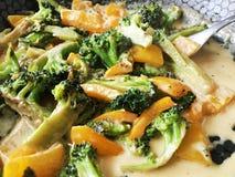 Vegetais com creme em uma bandeja quente, em uns brócolis e em uma pimenta doce Fotografia de Stock Royalty Free