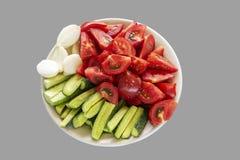 Vegetais cortados Tomates, pepinos e cebolas em um fundo cinzento Trajeto de grampeamento fotografia de stock royalty free