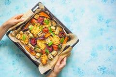 Vegetais cozidos em uma folha de cozimento nas mãos do ` s das mulheres fotografia de stock royalty free