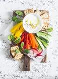Vegetais crus e molho do iogurte em uma placa de corte de madeira, em um fundo claro, vista superior Alimento saudável do vegetar Imagem de Stock