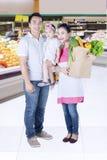 Vegetais da compra da família no supermercado Fotos de Stock