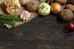 Vegetais da mola em um fundo escuro: cebola, alho, couve-rábano, raiz de aipo, aneto, beterrabas, batatas Fotografia de Stock Royalty Free