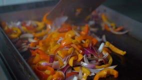 Vegetais de fritura e de mistura do cozinheiro chefe para o prato na grade aberta em um restaurante video estoque